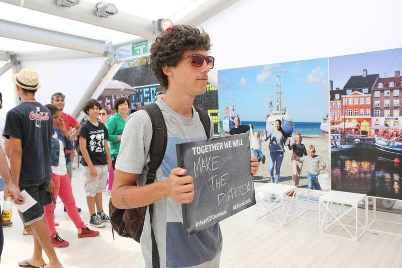 """Rapaz segura pequeno quadro negro escrito em inglês """"Juntos nós faremos a diferença"""""""