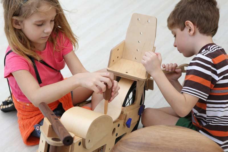 Crianças montando uma bicicleta de madeira