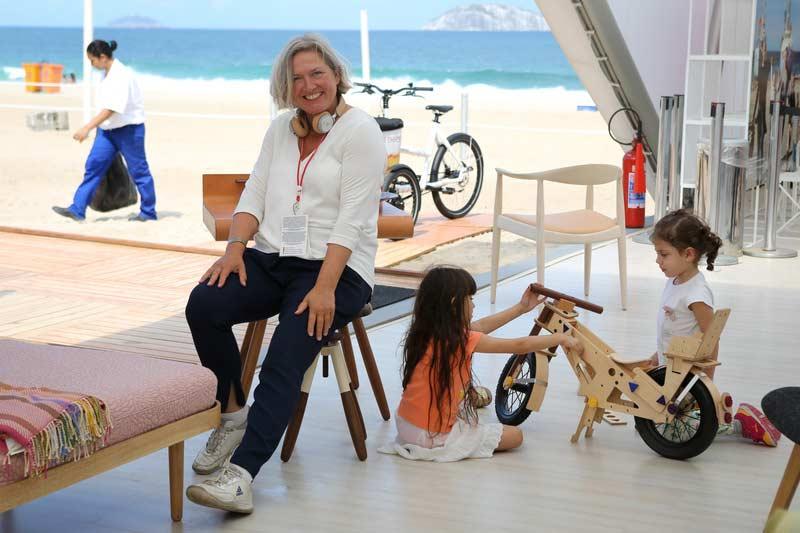 Expositora da Casa Dinamarca com crianças montando bicicleta de mandeira e a Praia de Ipanema ao fundo.