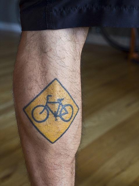 foto de tatuagem de placa de ciclovia na panturrilha