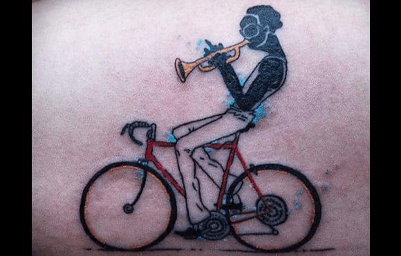 foto de tatuagem de pessoa tocando trompete e pedalando