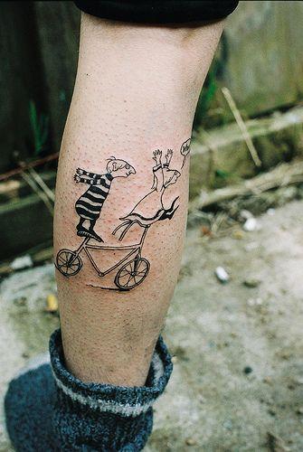 foto de tatuagem de dois personagens em pé em uma bicicleta