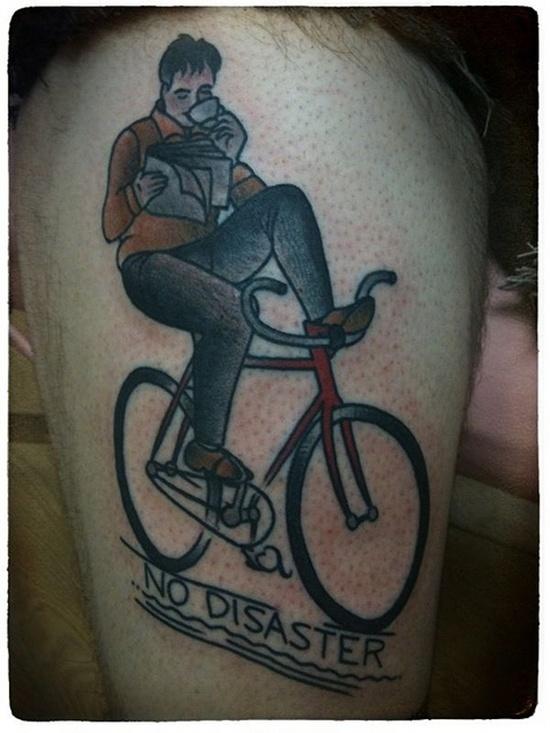foto de tatuagem old school de homem pedalando enquanto toma um café e lê um jornal