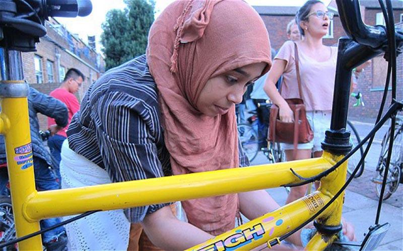 Mulher refugiada faz ajustes em sua bicicleta