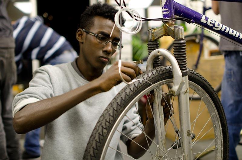 Jovem refugiado consertando bicicleta