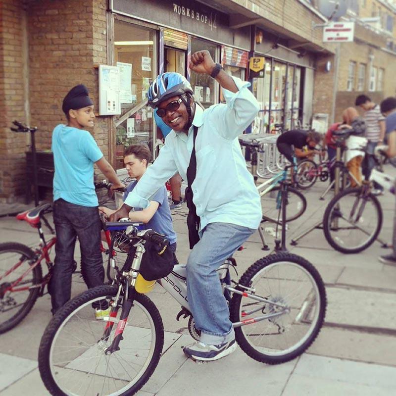 Homem refugiado pedala feliz a sua bicicleta