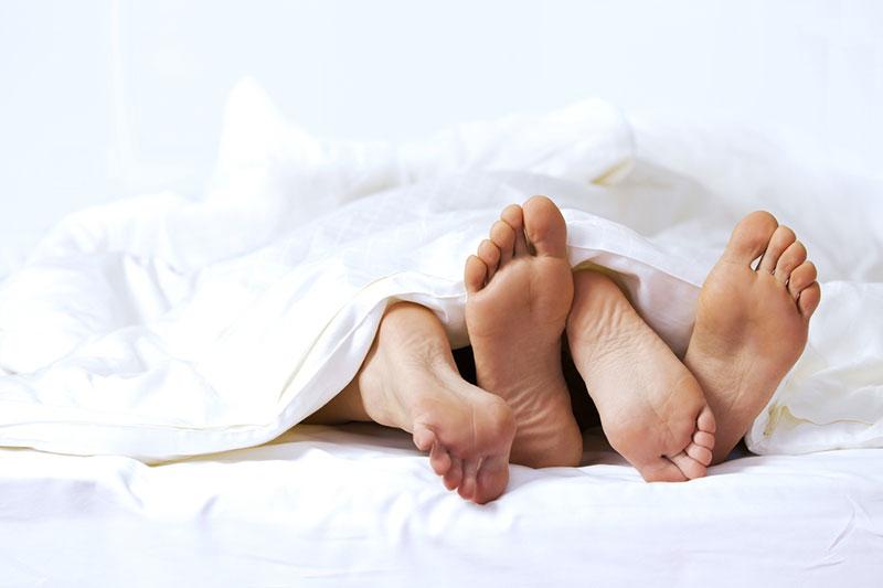 Sexo: pés de casal sob edredom